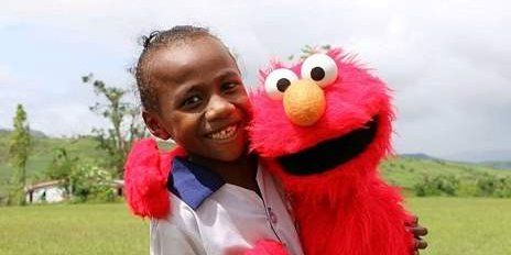 A child in Fiji with Elmo - puppets help kids smile again after Cyclone Winston