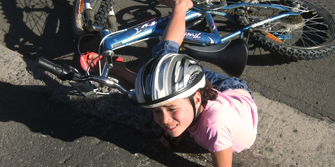 A girl falls off her bike and needs first aid care