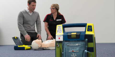 A first aid instructor demonstrates how to use an AED
