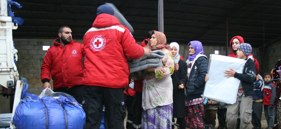 Red Cross volunteers hand out blankets and relief supplies