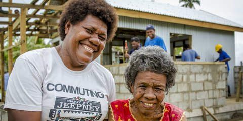 Lusiana and her mother, Makarita, watch as Red Cross rebuilds their home in Nukubalavu, Fiji