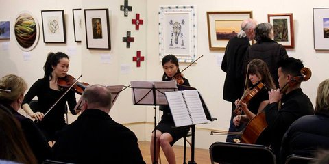 Violinists play at an art auction for Red Cross in Dunedin