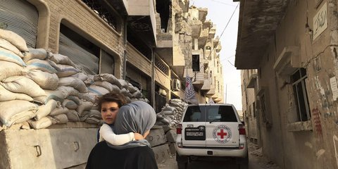 A mother carries her child in Homs