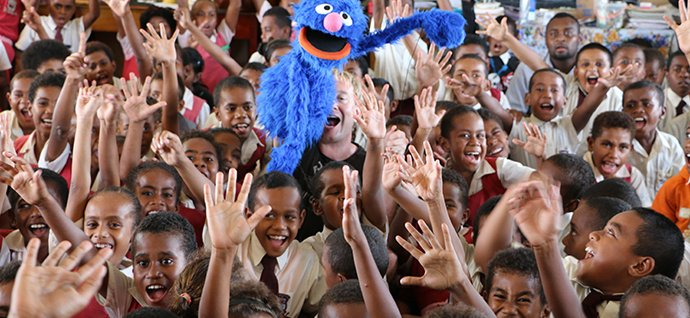 Fiji kids having fun with a Sesame Street puppet